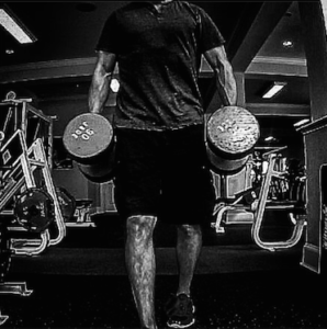 Coach Brandon performing farmer's walks with a pair of dumbbells