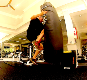 Brandon performing some HIIT training by delivering some knee strikes to a long bag.