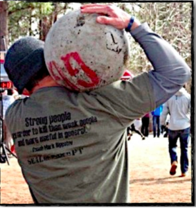 A guy carrying an atlas stone on his shoulder displaying functional fitness